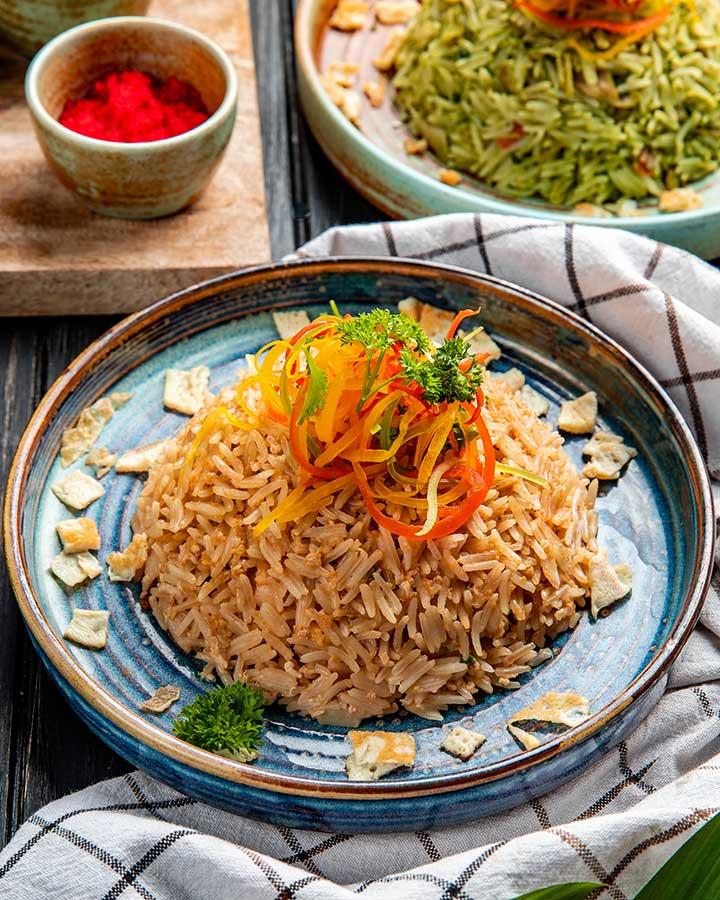 Vedere laterală a orezului japonez prăjit cu legume în sos de soia pe o farfurie